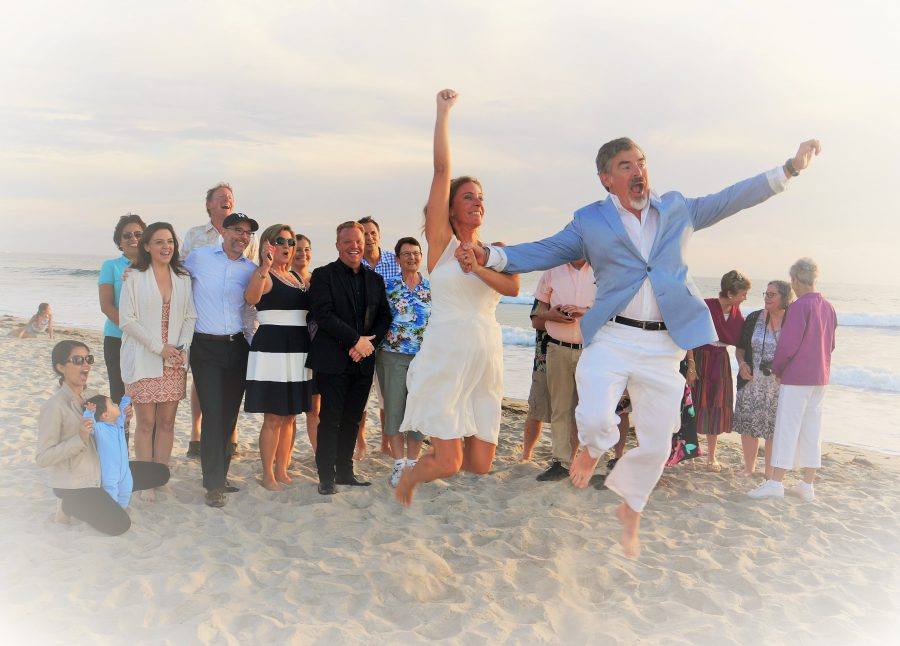 couple jumps for joy on the beach after they are married