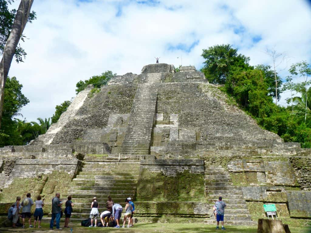man stands on mayan ruins as tourists mill about on the ground