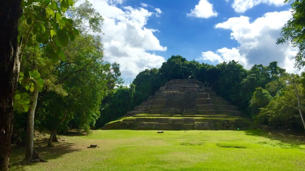 beautiful mayan ruins against trees and blue sky with clouds at lamanai