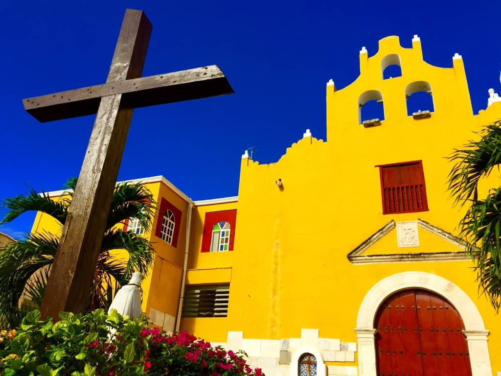 colorful yellow church in campeche against a bright blue sky