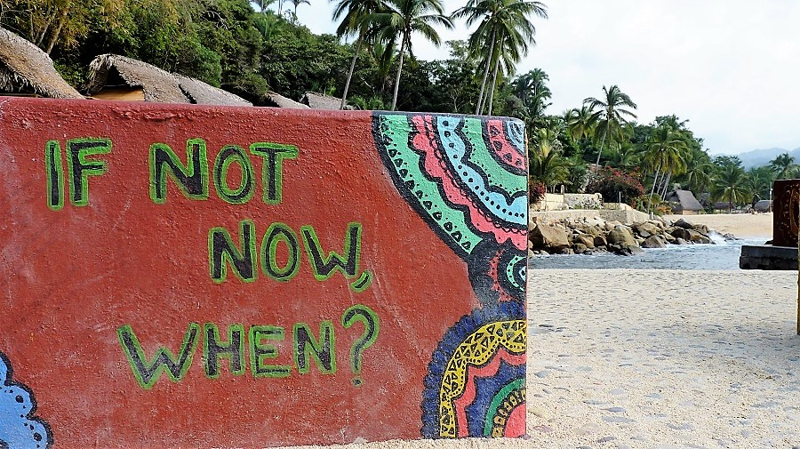 "a sign on a beach reads, ""If not now, when?"" and refers to travel the world in retirement"