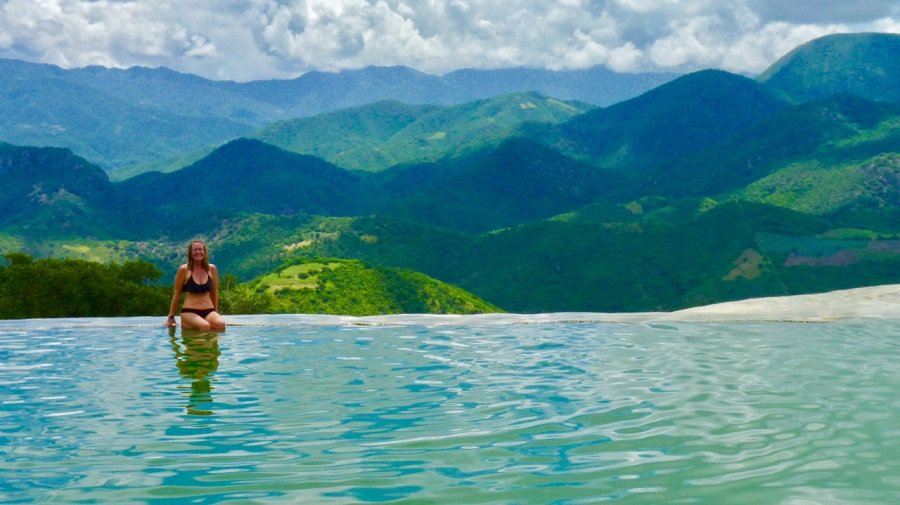 Ellen in mineral water in an infinity pool overlooking a lush, green valley in Oaxaca, Mexico, at the remote Hierve el Agua site.