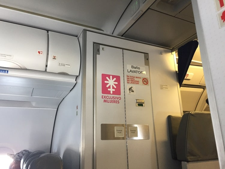 picture of airplane bathroom door that says 'women only' on Interjet, one of the mexican airlines