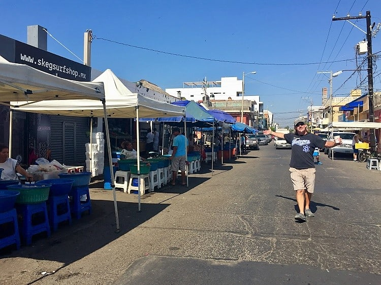 wide shot down the street where people sell fresh fish, including the shrimp ladies in mazatlan