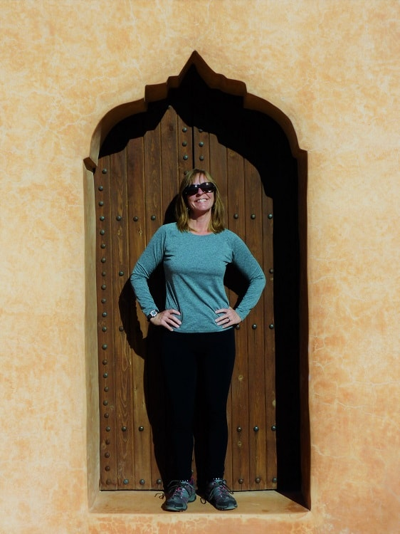 A woman poses in a doorway for a picture while walking around - the most obvious budget things to do in Marrakesh.
