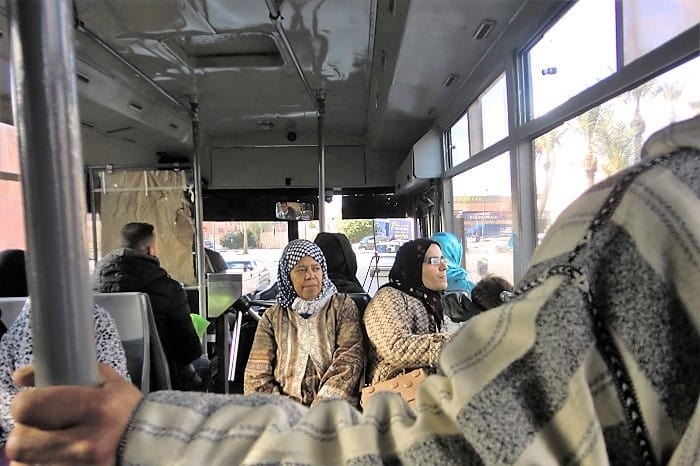 muslim women ride a public bus into a marrakesh neighborhood outside the old, walled-off city