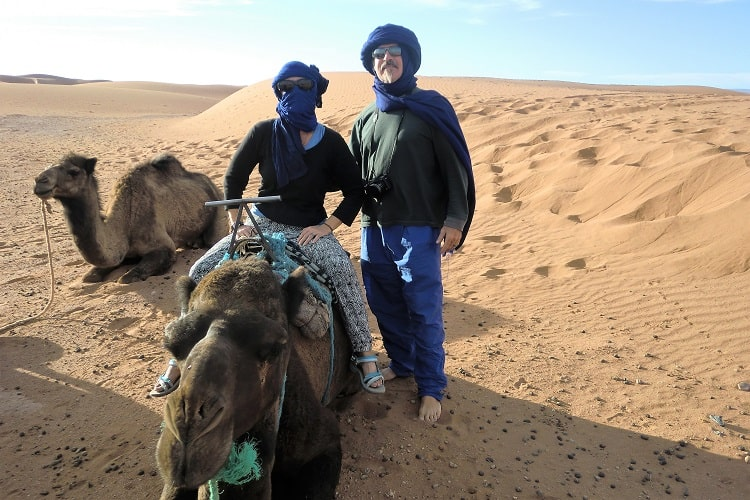 Two people and two camels in the Sahara Desert enjoy the 'retire early' world travel lifestyle.
