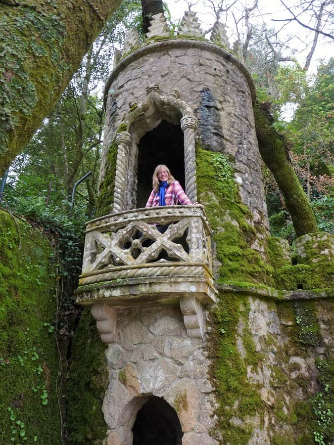 a woman stands on a palace balcony in sintra