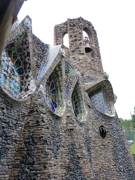 a small tower with a bell at the unfinished level of another church built by gaudi
