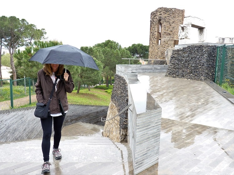 a woman stands in the rain on the main floor of what gaudi intented to be the main church, but he never finished construction