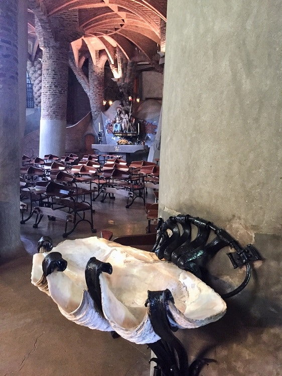 a stand that holds holy water that looks like a giant shell, in another church built by gaudi