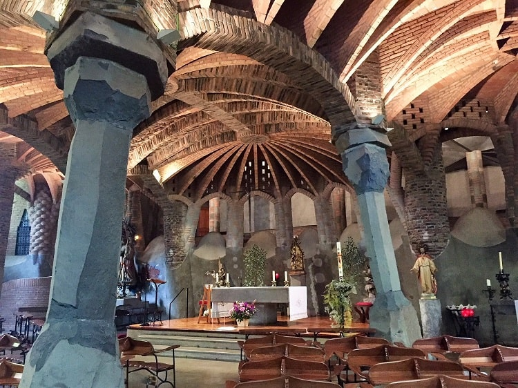 a closer look at the soaring ceiling and tree-like pillars inside another church built by gaudi before la sagrada familia