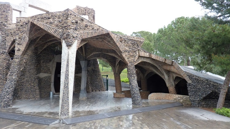 another church gaudi built in Colonia Guell that shows columns that look like trees, similar to la sagrada familia in barcelona