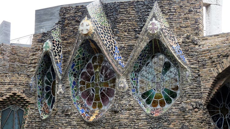 strange stained glass windows surrounded by bits of cut-glass in the facade of another church built by architect antoni gaudi