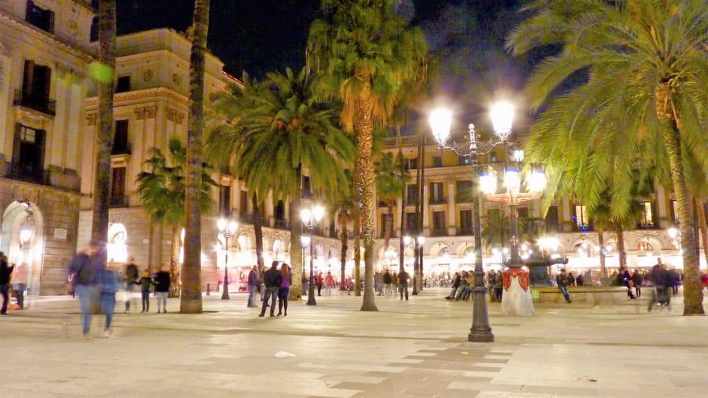dining on placa reial is one of the activity ideas for barcelona. this is a wide shot of the plaza at night showing restaurants around the perimeter