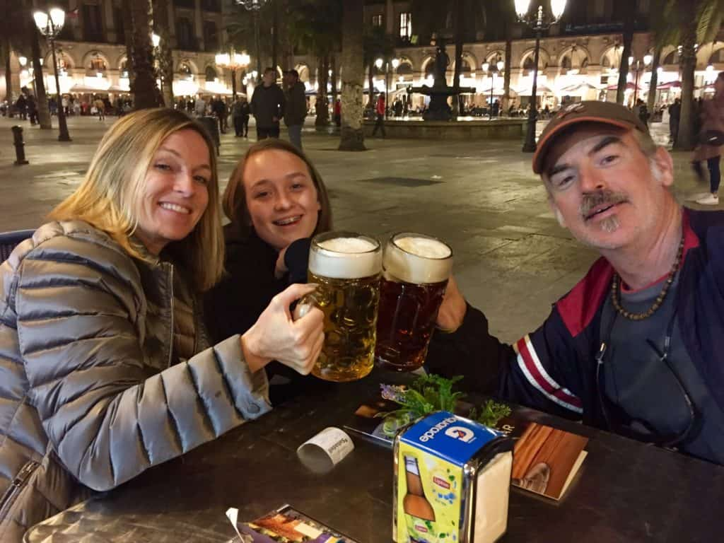 here, a man and woman hold up mugs of beer in a toast at plaza reial