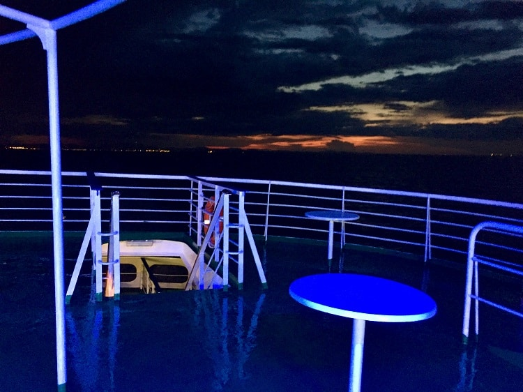 an upper back deck bathed in blue light at sunset on the ferry from italy to croatia