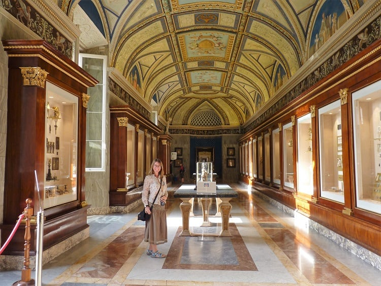 Woman smiles at Vatican Museums, happy to do budget travel in Rome.