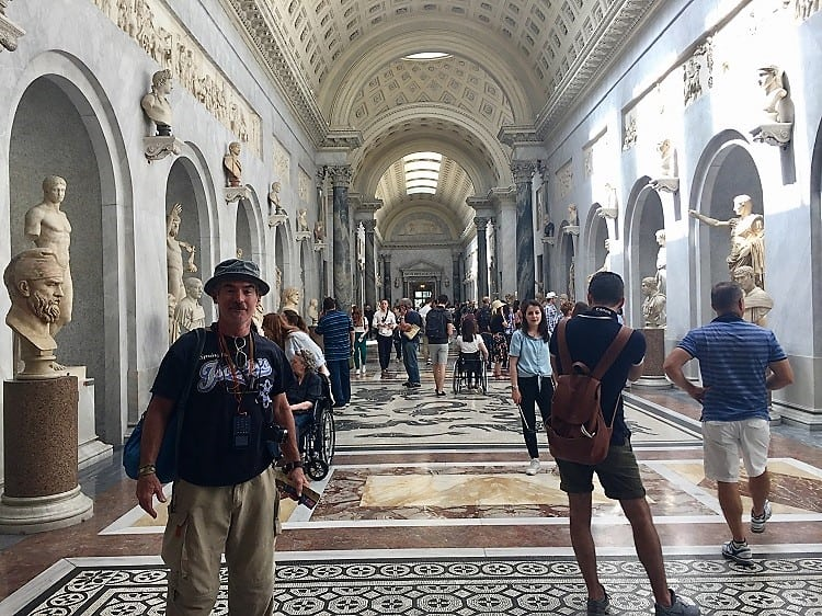 Man stands in Vatican Museums, happy to see art during budget travel in Rome.