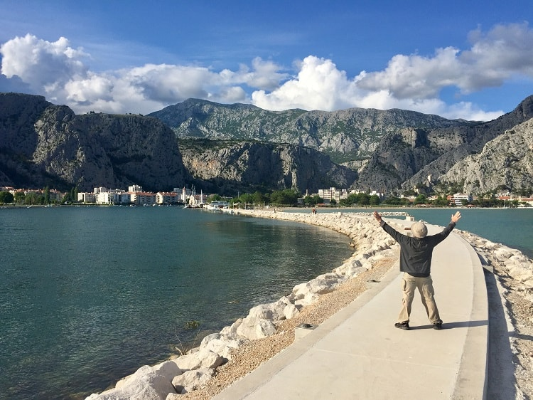 man poses for picture on sea walkway in omis croatia
