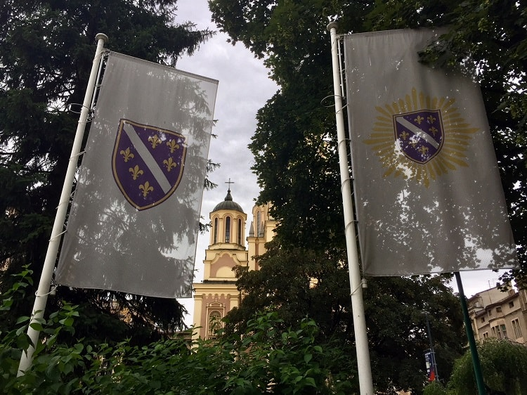 Sarajevo's main orthodox cathedral tower pictured between two flags is one of the sights on one of the walking tours in sarajevo