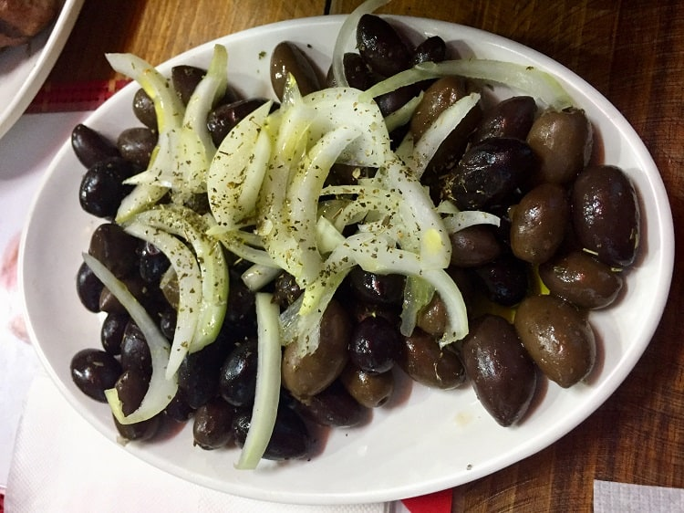 a plate of black olives with onions and a dab of olive oil brine in tirana