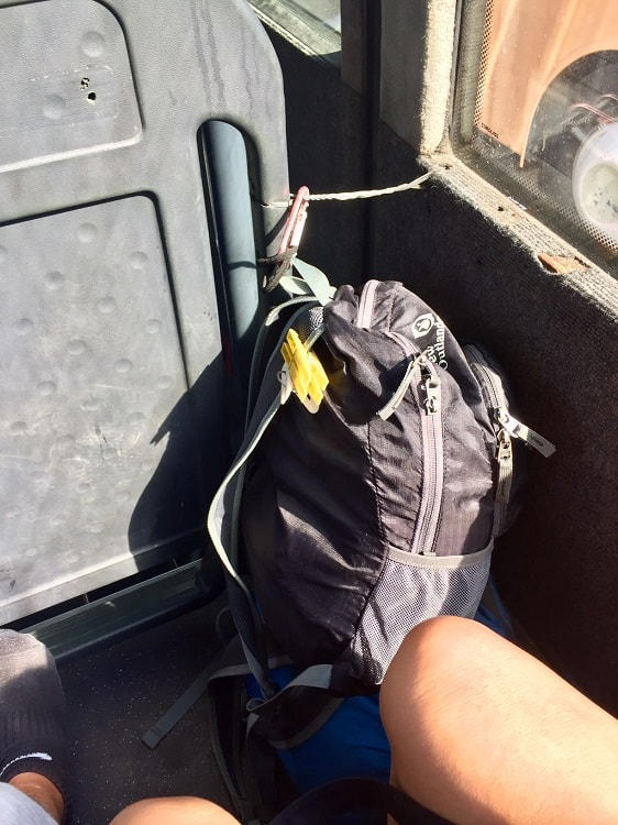 carabiner clips backpack to the seat for stability on the bus from montenegro to albania