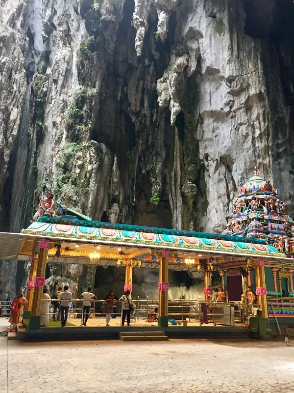 an open-air hindu temple painted in many colors inside the batu caves