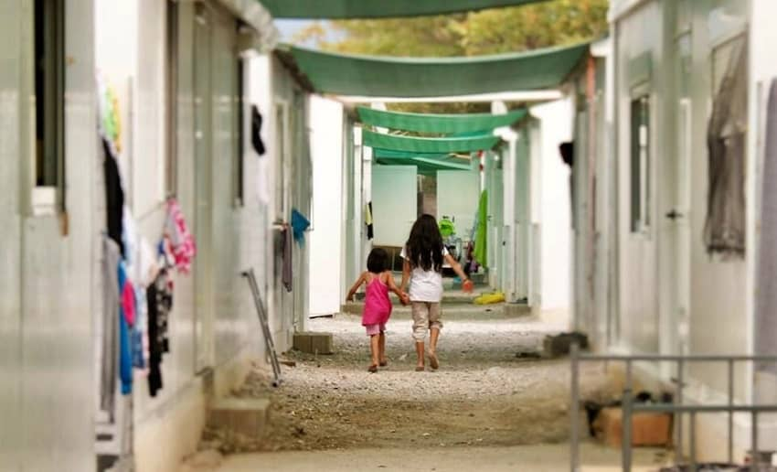 Kids walk among temporary homes in Eleonas Camp for refugees in Athens, Greece.