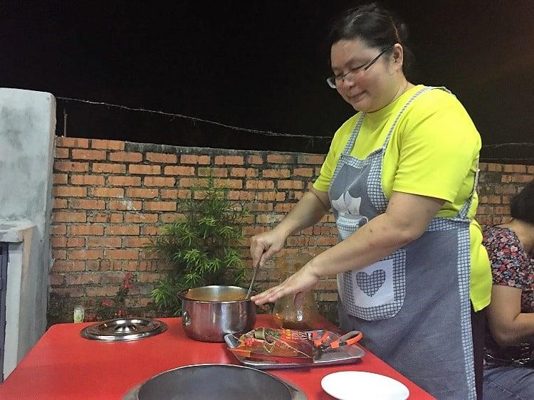 a woman prepares peanut oil to cook satay - a popular malaysian food