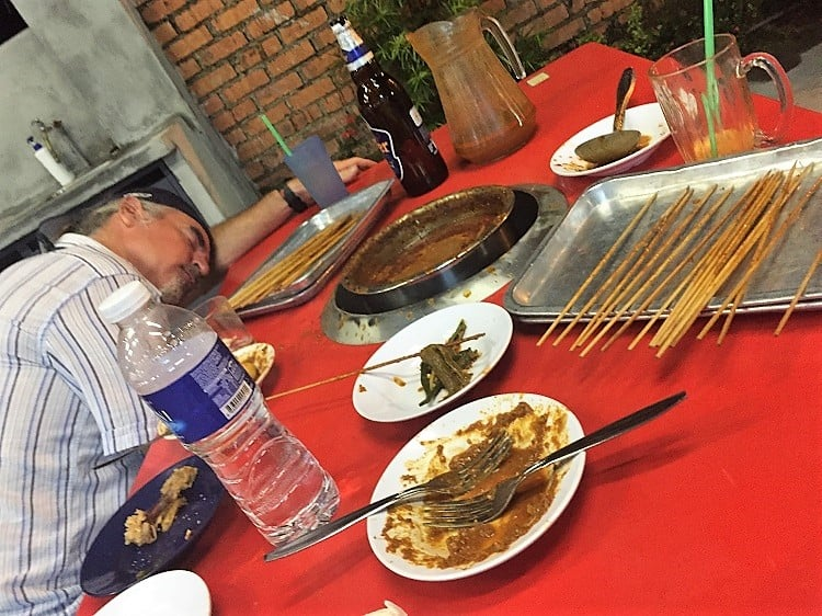 a dining table filled with items for satay, which is malaysian food