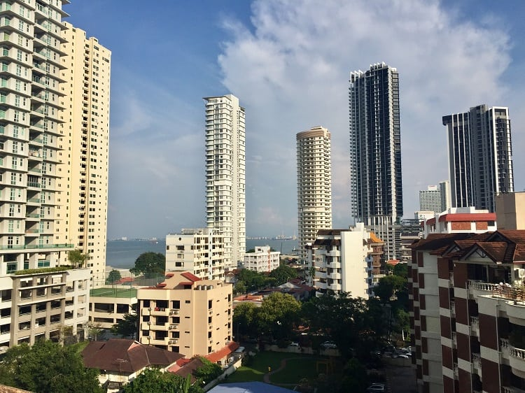 the george town skyline is filled with high rise apartment buildings for expats in malaysia