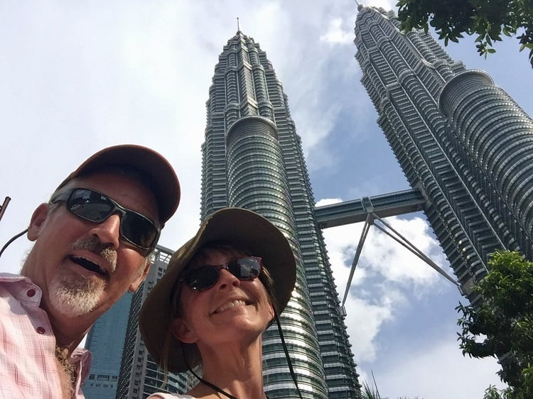 Two people in front of the iconic twin towers in Kuala Lumpur, Malaysia - how to retire early and travel the world