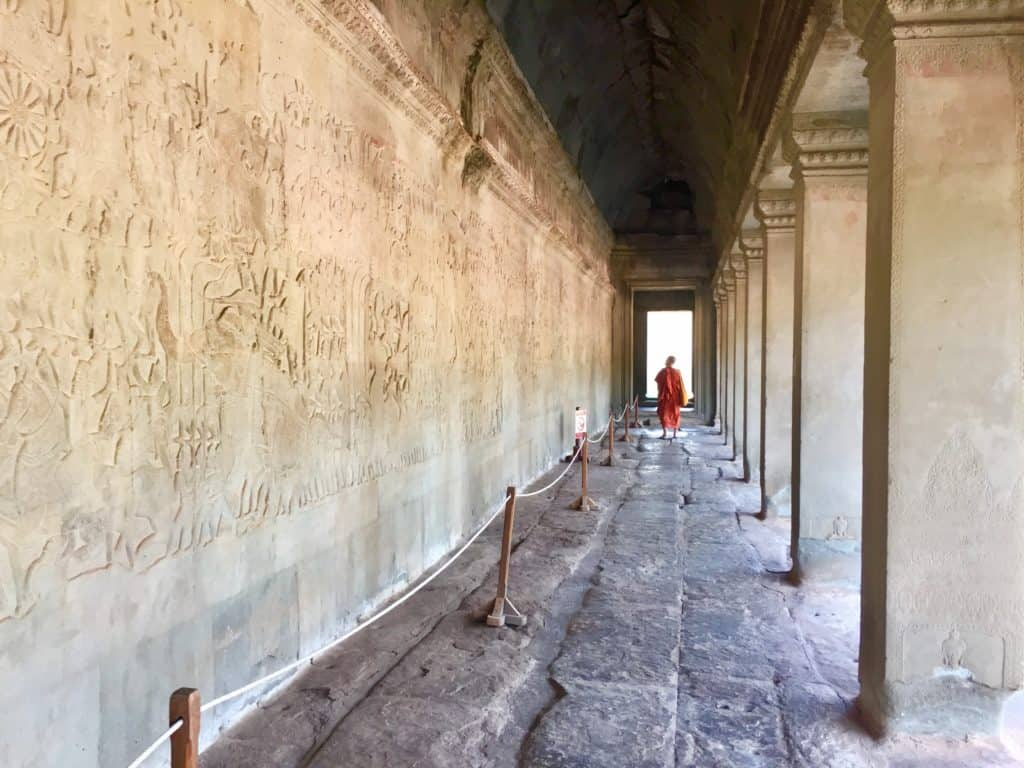 a monk wanders down a row of steli relief that tells the story of creation at Angkor Wat