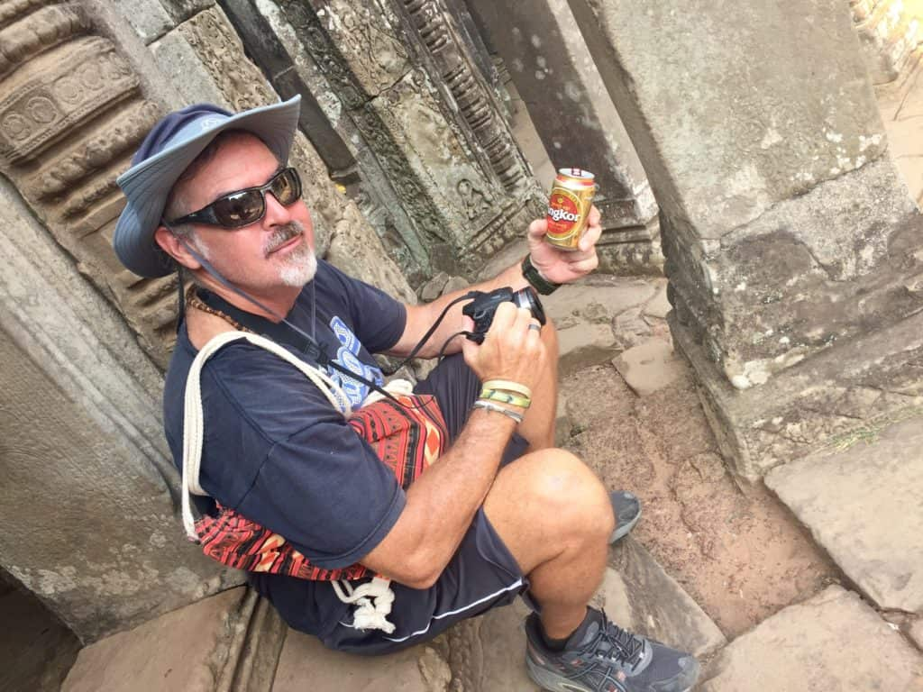 Angkor Wat budget travel tips- a man drinks a beer at a temple entrance