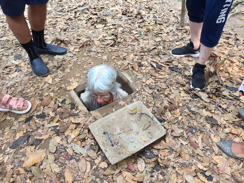 a woman squeezes into the opening of the cu chi tunnels