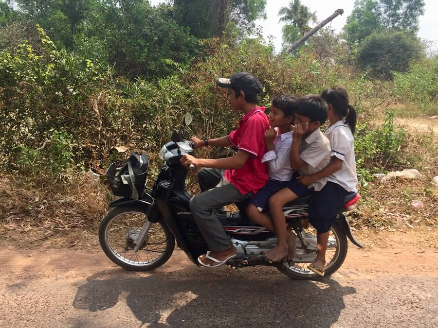 four kids ride a scooter