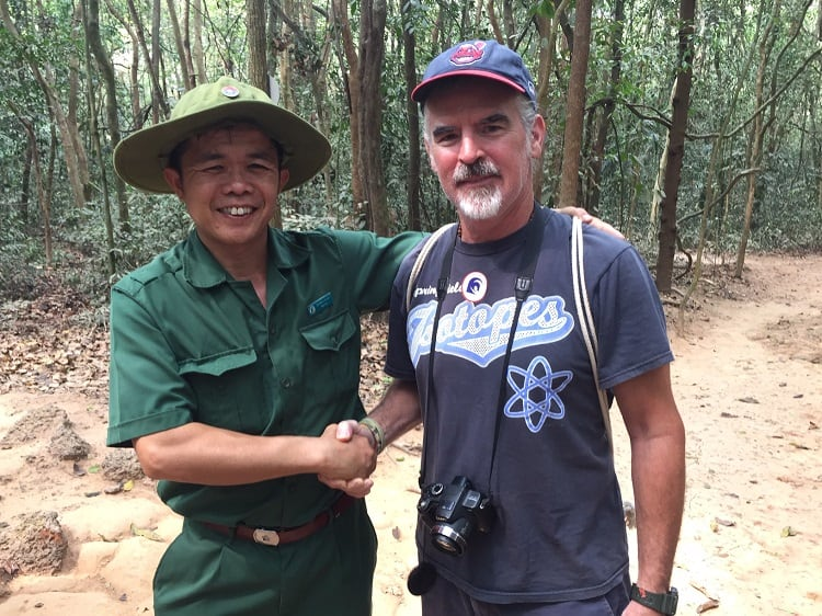 a vietnamese tour guide and a tourist shake hands outside the cu chi tunnels in the jungle