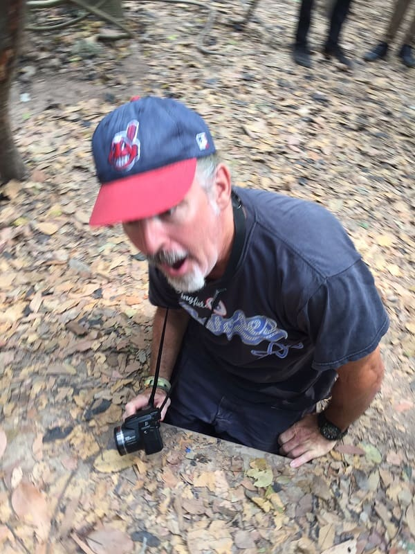 a man tries to squeeze into an opening into the cu chi tunnels in the middle of the jungle