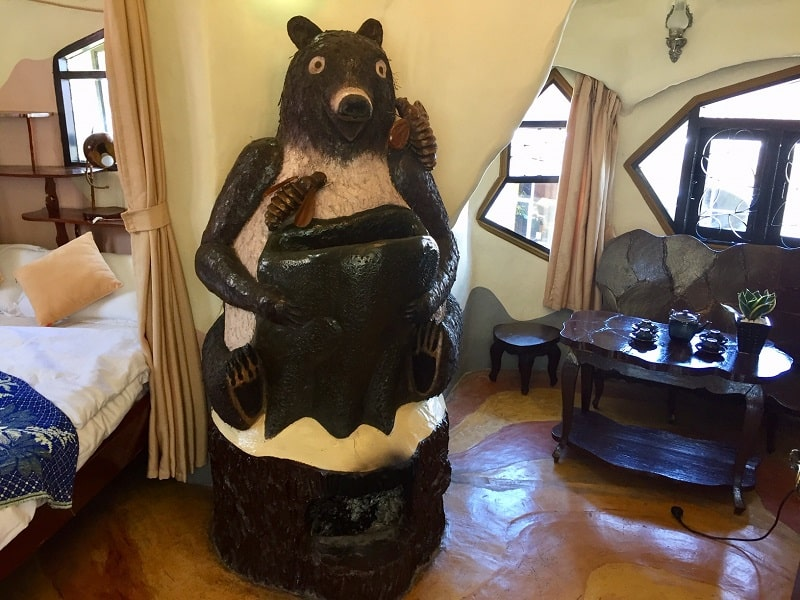 the bear room at the crazy house has a large wooden grizzly bear
