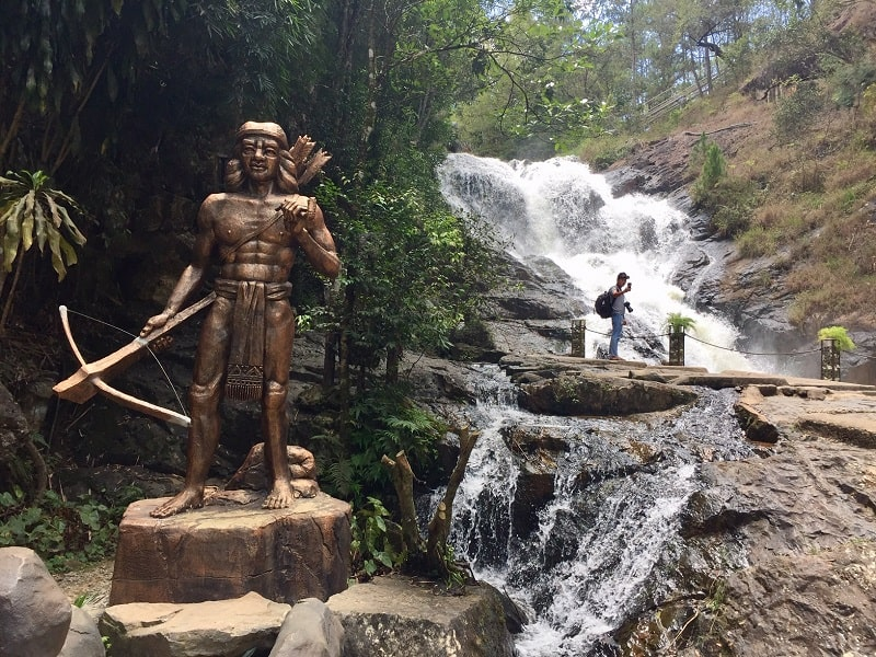a statue of a native person at the dalat waterfall