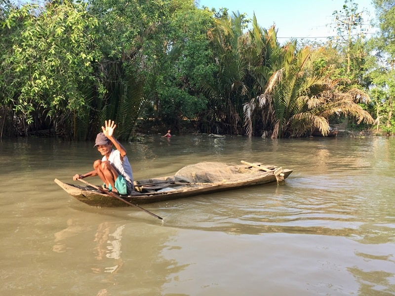 man waves hello from his row boat on the mekong delta in vietnam