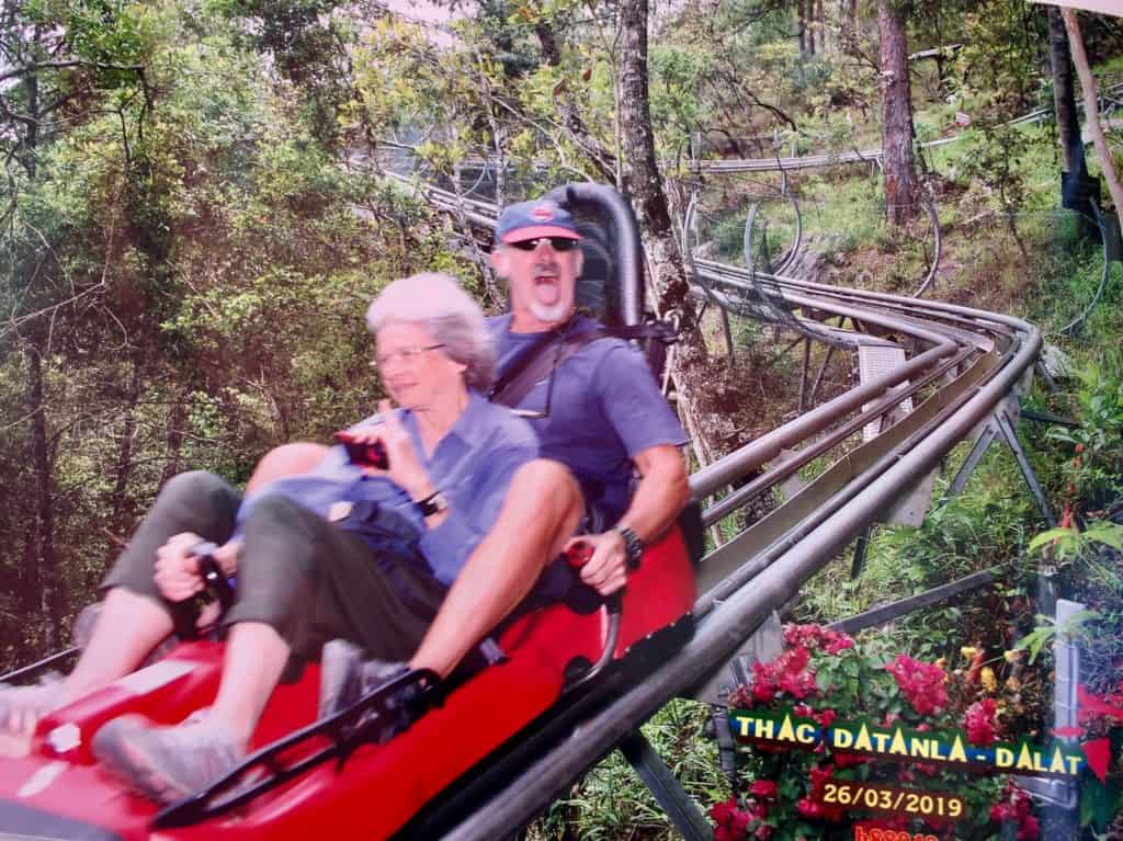 a man and his mom smile as they zoom by on the dalat roller coaster