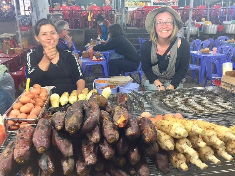 two women sit in front of smoked sweet potatoes at the dalat night market