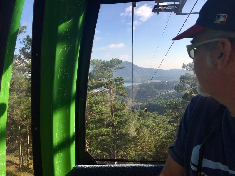 a man looks out of the dalat cable car
