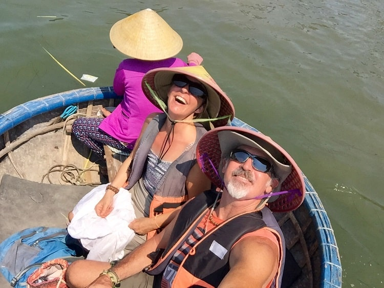 three people in Vietnamese style hats in a so-called 'basket boat'