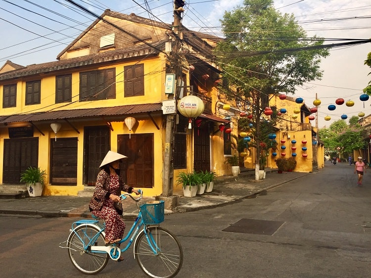 a vietnamese woman on a bicycle in hoi an