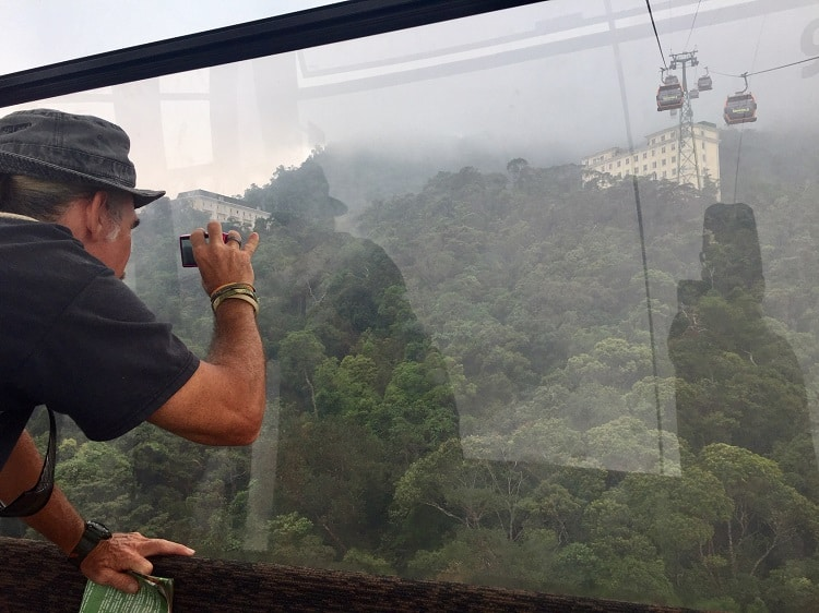 man takes pictures from cable car up to Ba Na Hills