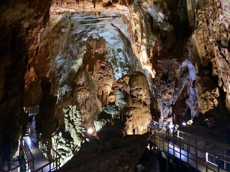A walkway looks tiny inside a giant Phong Nha cave.