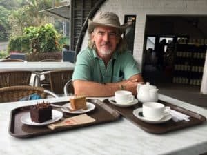 A man sits with cakes and tea at a tea plantation in Cameron Highlands, Malaysia.
